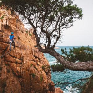girl climbing on via ferrata sant feliu guixols catalunya spain